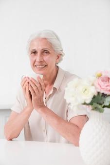 Portrait de femme senior souriante tenant une tasse de café