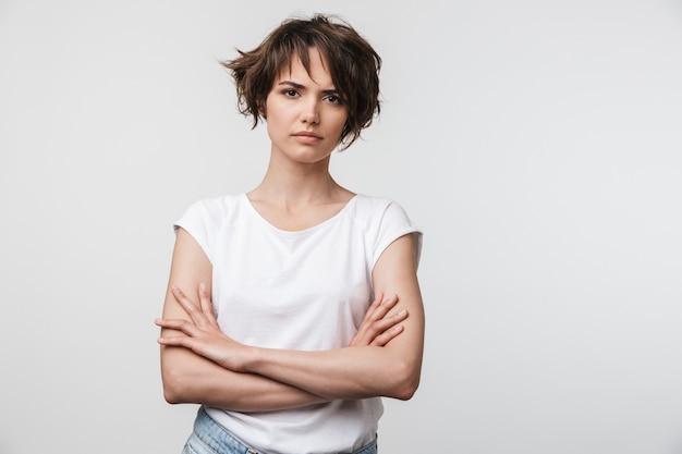 Portrait de femme sérieuse aux cheveux bruns courts en t-shirt basique fronçant les sourcils isolé sur mur blanc