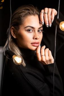 Portrait de femme sérieuse en pull noir debout et posant