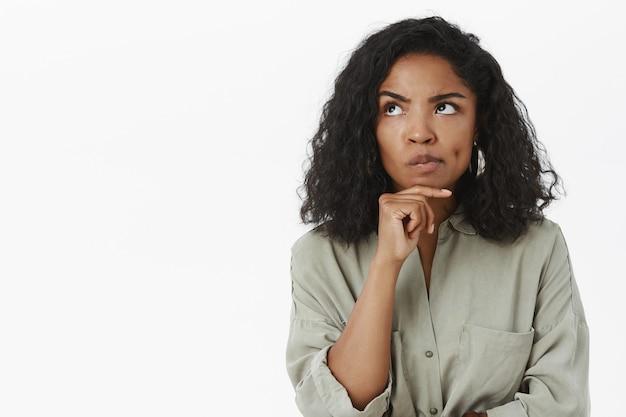 Portrait de femme sérieuse réfléchie et intelligente, souriant et fronçant les sourcils en levant la main sur le menton