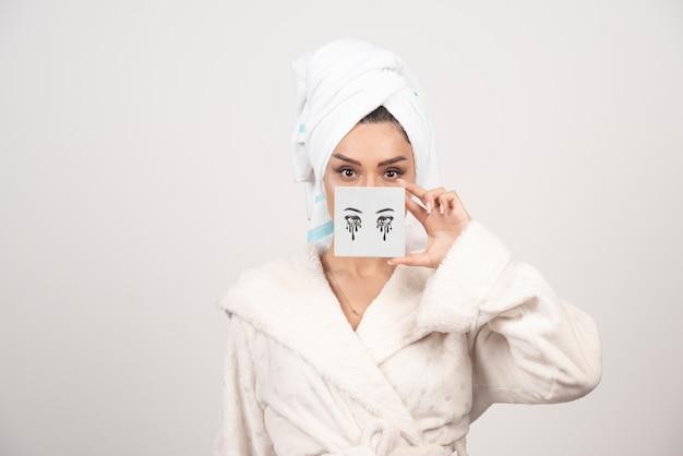 Portrait de femme en serviette blanche avec palette d'ombres à paupières