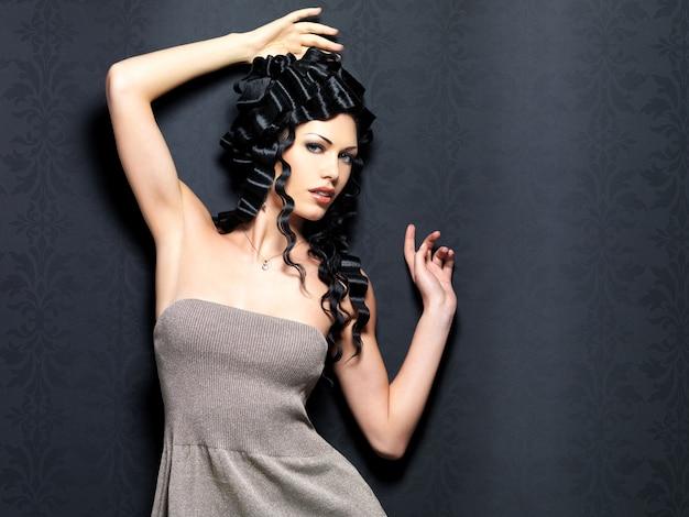 Portrait de la femme sexy belle mode avec une longue coiffure frisée pose à l'intérieur