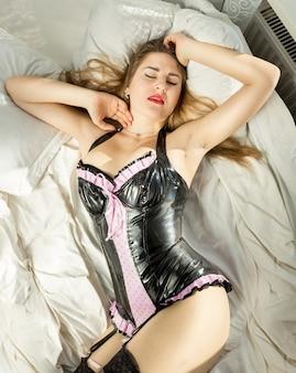 Portrait de femme sexy en corset latex couché dans son lit