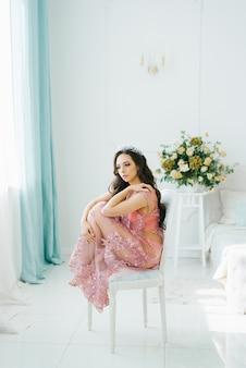 Portrait de femme sexy à la peau douce, vêtue d'une lingerie sexy en dentelle rose. belle fille assise sur une chaise blanche