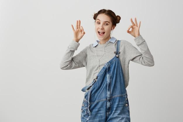 Portrait de femme en signe gesticulant décontracté avec les deux mains. clientèle excitée exprimant sa joie après avoir parlé avec un opérateur mobile à travers des écouteurs. émotions humaines