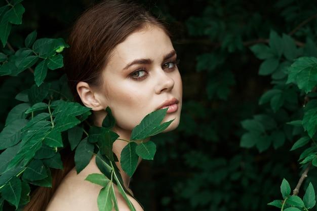 Portrait d'une femme soins de la peau épaules nues feuilles vertes mode de vie nature