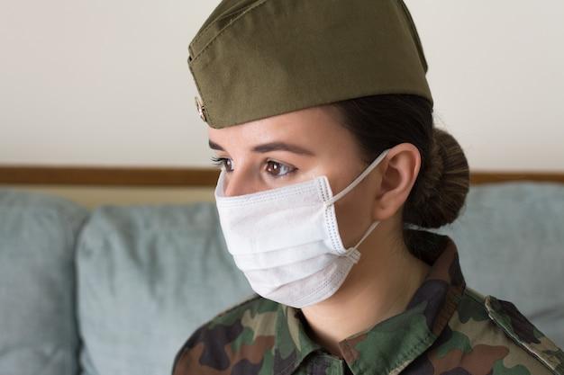 Portrait d'une femme soldat en uniforme et masque chirurgical