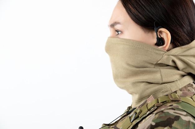 Portrait de femme soldat en uniforme militaire sur mur blanc