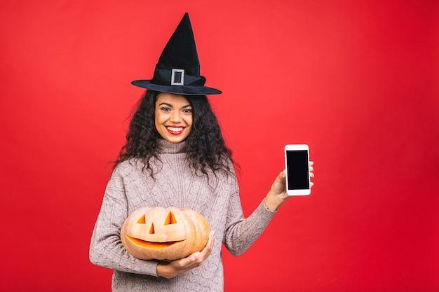 Portrait de femme sorcière afro-américaine halloween tenant une citrouille