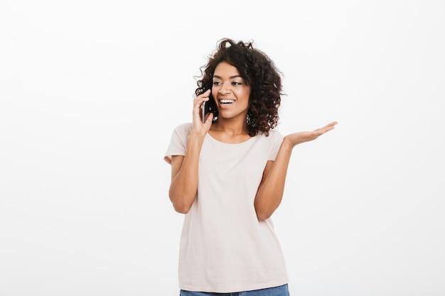 Portrait d'une femme souriante adorable avec une coiffure à la mode portant des jeans et t-shirt, parler au téléphone mobile et faire des gestes émotionnellement, isolé sur un mur blanc