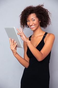 Portrait d'une femme souriante à l'aide d'un ordinateur tablette sur un mur gris