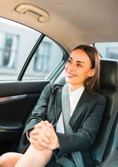 Portrait d'une femme souriante assise à l'intérieur d'une voiture
