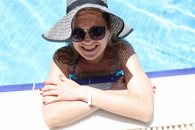 Portrait de femme souriante au chapeau et lunettes de soleil dans la piscine
