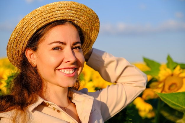 Portrait d'une femme souriante au chapeau de paille dans le champ de tournesol en fleurs