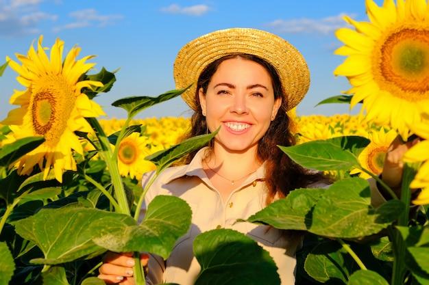Portrait d'une femme souriante au chapeau de paille avec fleur de tournesol dans un champ