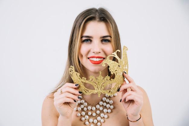 Portrait d'une femme souriante au collier tenant un masque de carnaval doré