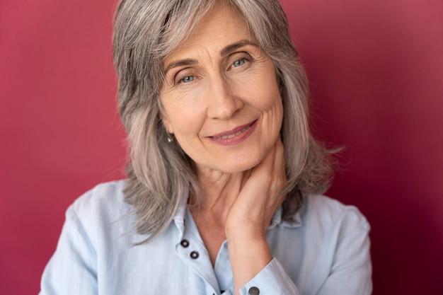 Portrait de femme souriante aux cheveux gris senior