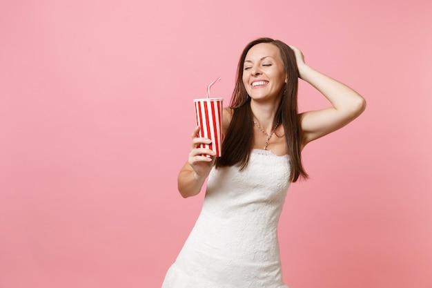 Portrait d'une femme souriante aux yeux fermés en robe blanche gardant la main sur la tête tenant une tasse en plastique avec du cola ou du soda