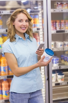 Portrait d'une femme souriante ayant sur ses mains son smartphone et son fromage à la crème