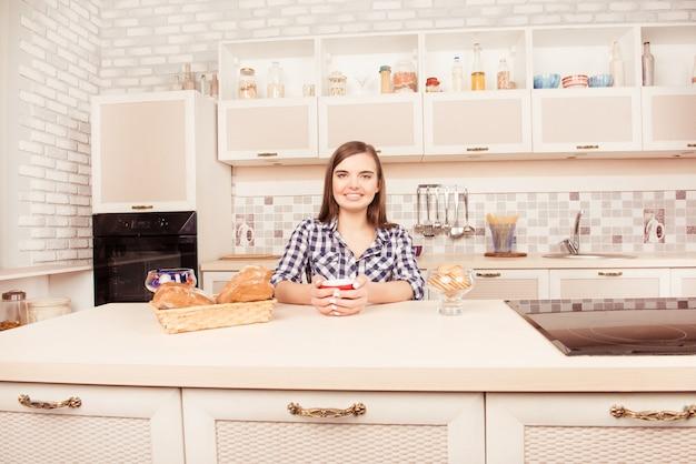 Portrait de femme souriante, boire du café avec des gâteaux cuits au four