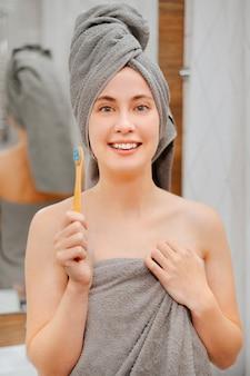 Portrait d'une femme souriante avec une brosse à dents écologique dans la salle de bain. soins bucco-dentaires.