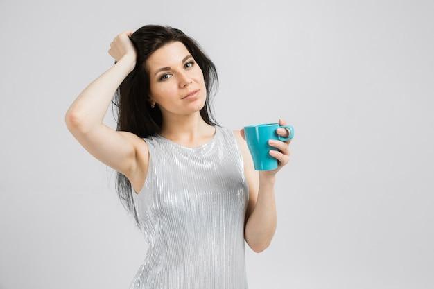 Portrait de femme souriante brunet en chemisier tenant une tasse