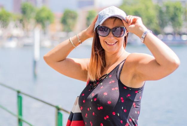 Portrait d'une femme souriante avec chapeau au bord du lac