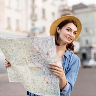 Portrait de femme souriante avec chapeau tenant la carte