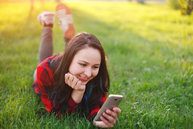 Portrait, de, a, femme souriante, coucher herbe verte, et, utilisation, smartphone, dehors