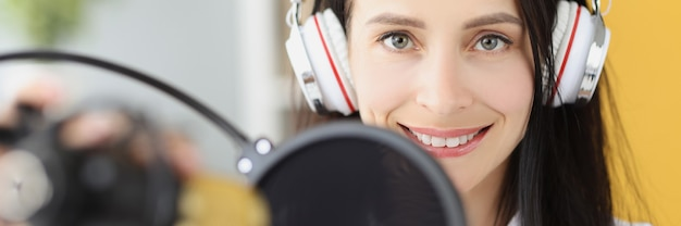 Portrait de femme souriante dans les écouteurs devant le microphone en studio