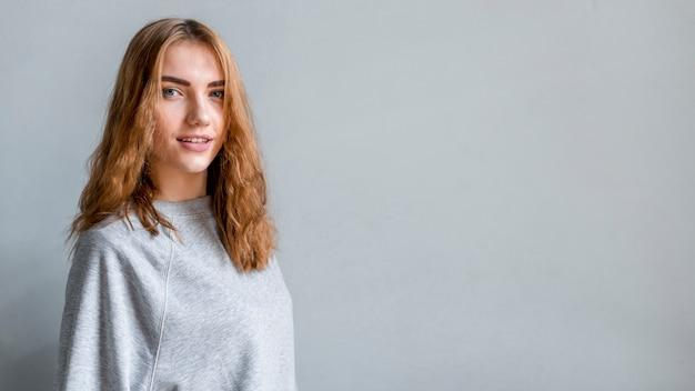 Portrait, de, a, femme souriante, debout, contre, gris, mur, regarder appareil-photo