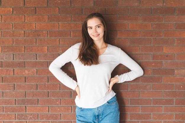 Portrait de femme souriante devant un mur de briques - belle brune debout et regardant la caméra - portrait candide d'une belle jeune femme à londres