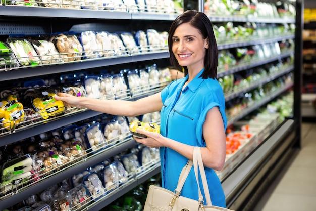 Portrait d'une femme souriante faisant des courses