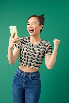 Portrait d'une femme souriante faisant selfie photo sur smartphone isolé sur vert