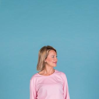 Portrait d'une femme souriante sur fond bleu
