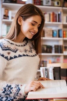 Portrait d'une femme souriante heureuse lisant un livre dans la bibliothèque