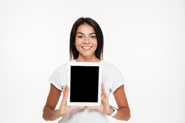 Portrait d'une femme souriante heureuse montrant une tablette écran vide