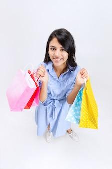 Portrait d'une femme souriante heureuse avec de nombreux forfaits commerciaux isolés sur blanc