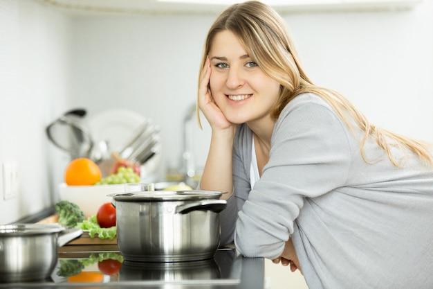 Portrait de femme souriante heureuse posant sur la cuisine et la cuisson de la soupe