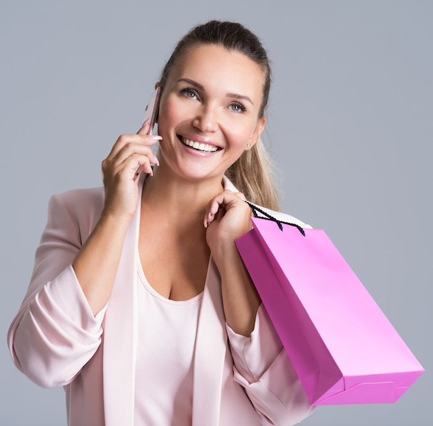 Portrait de femme souriante heureuse avec sac à provisions rose qui parle sur un téléphone mobile.
