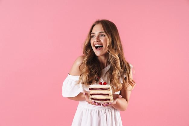 Portrait d'une femme souriante heureuse vêtue d'une robe blanche regardant de côté et tenant un morceau de gâteau isolé sur un mur rose