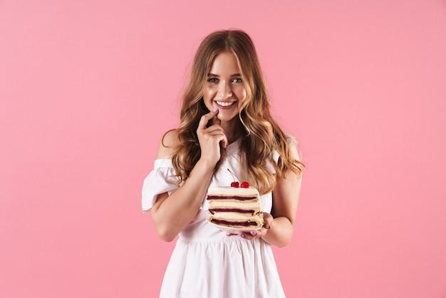 Portrait d'une femme souriante heureuse vêtue d'une robe blanche regardant de face avec son doigt sur son menton et tenant un morceau de gâteau isolé sur un mur rose