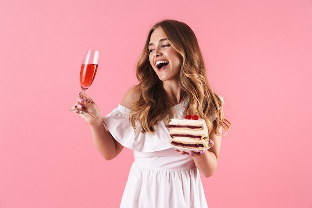 Portrait d'une femme souriante heureuse vêtue d'une robe blanche regardant un verre de vin et tenant un morceau de gâteau isolé sur un mur rose