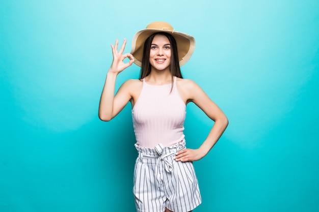 Portrait de femme souriante heureuse vêtue d'une robe, chapeau d'été de paille montrant le geste ok, espace de copie de signal de pouces isolé sur le mur bleu. espace publicitaire