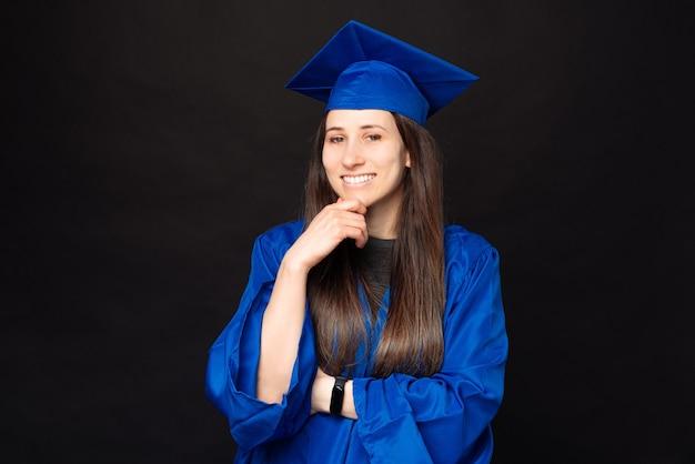Portrait de femme souriante jeune étudiante gaie portant baccalauréat et chapeau de graduation sur fond noir