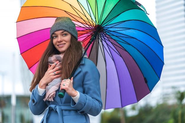 Portrait de femme souriante joyeuse insouciante heureuse dans des vêtements chauds avec un parapluie arc-en-ciel de couleur vive pendant la journée pluvieuse et le temps de pluie en automne. protection contre la pluie