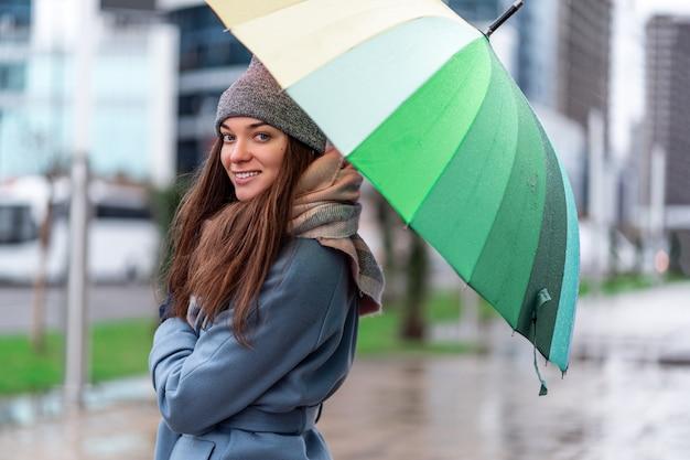 Portrait de femme souriante joyeuse insouciante heureuse dans des vêtements chauds avec un parapluie arc-en-ciel multicolore lumineux pendant la journée pluvieuse et le temps de pluie à l'automne dans la ville. protection contre la pluie
