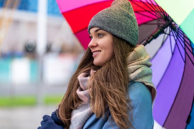 Portrait de femme souriante joyeuse insouciante heureuse dans des vêtements chauds avec un parapluie arc-en-ciel multicolore lumineux pendant la journée pluvieuse et le temps de pluie en automne. protection contre la pluie