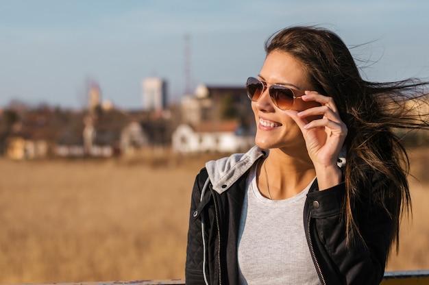 Portrait d'une femme souriante, lunettes de soleil à l'extérieur