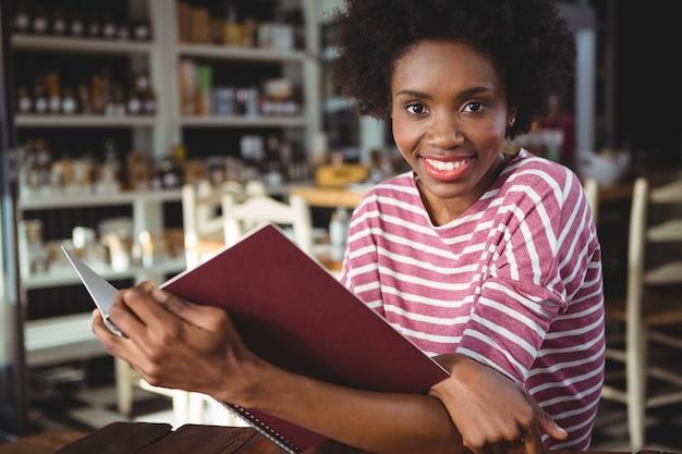 Portrait, de, femme souriante, menu lecture, dans, café